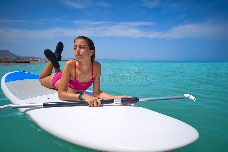 Girl relaxed lying on paddle surf board SUP. Relaxed in summer royalty free stock photo