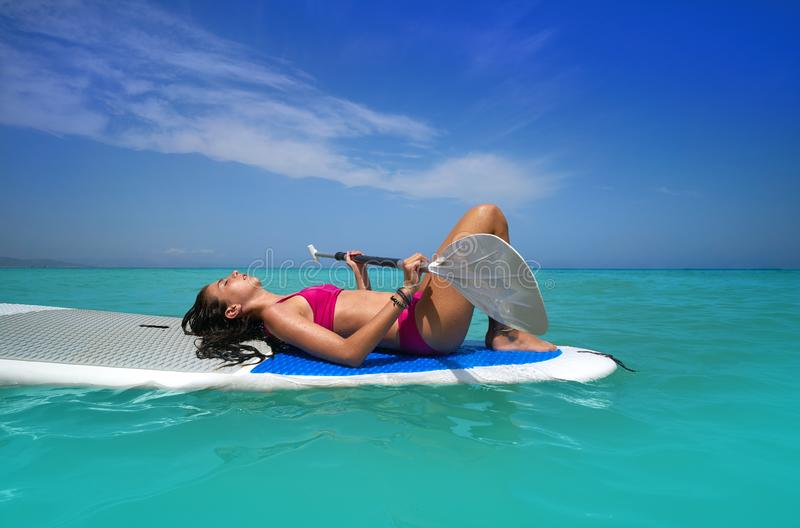 Girl relaxed lying on paddle surf board SUP. Relaxed in summer stock image