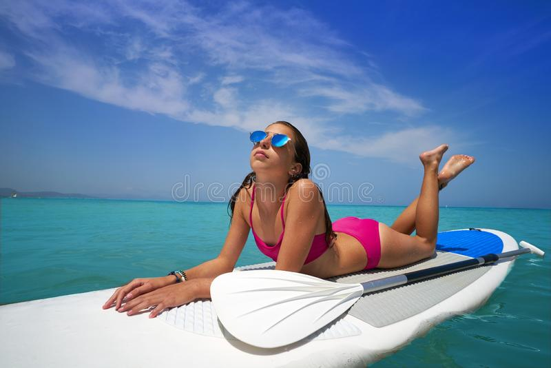 Girl relaxed lying on paddle surf board SUP. Relaxed in summer stock photos
