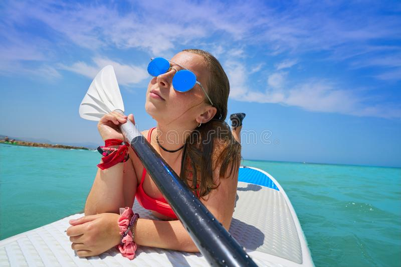 Girl relaxed lying on paddle surf board SUP royalty free stock photography