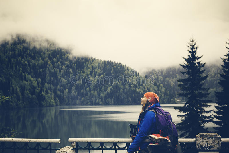 Girl relaxes on a background lake with mountains. Hiking and backpack resting. Travel Lifestyle concept journey. Satisfied and ha royalty free stock photo