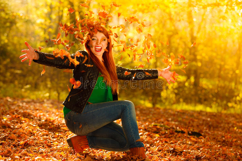 Girl relaxing in autumn park throwing leaves up in the air. Happiness carefree leisure concept. Redhaired long hair woman relaxing in autumn park throwing stock photo