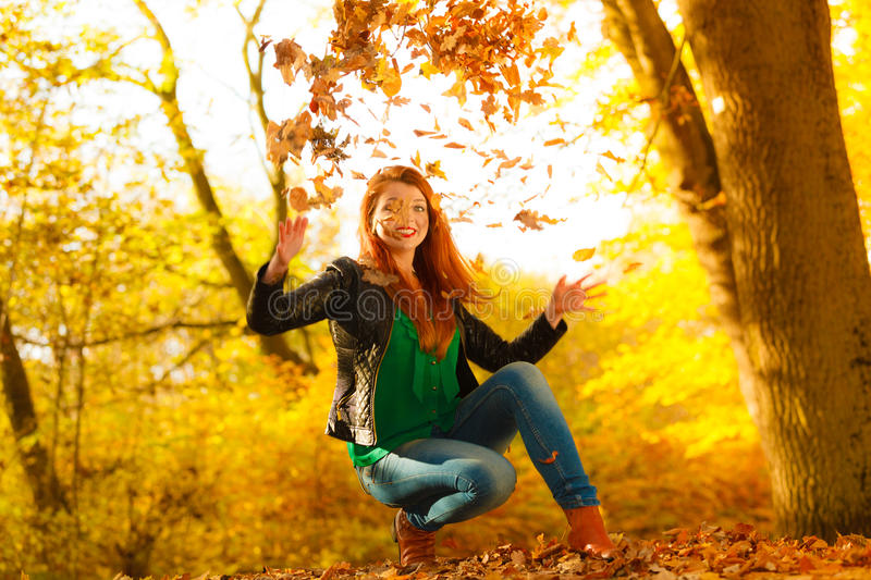 Girl relaxing in autumn park throwing leaves up in the air. Happiness carefree leisure concept. Redhaired long hair woman relaxing in autumn park throwing royalty free stock photos