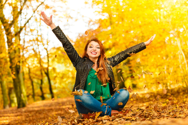Girl relaxing in autumn park throwing leaves up in the air. Happiness carefree leisure concept. Redhaired long hair woman relaxing in autumn park throwing royalty free stock photo