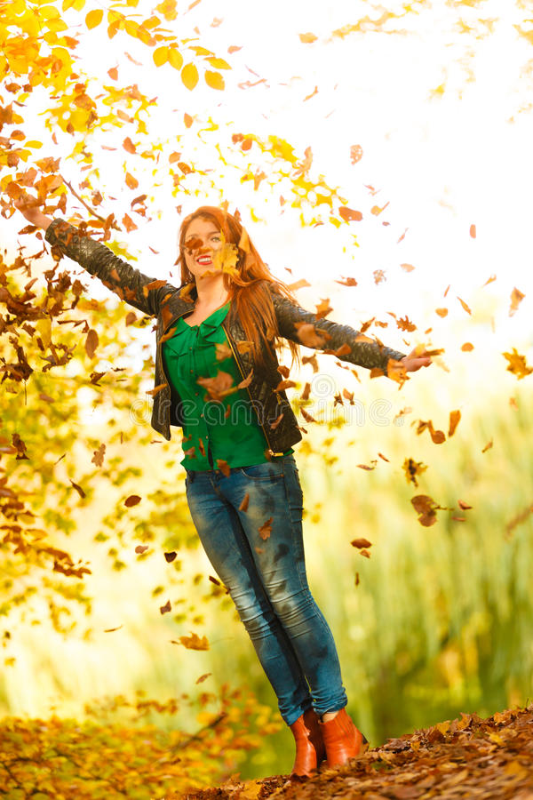 Girl relaxing in autumn park throwing leaves up in the air. Happiness freedom leisure concept. Redhair woman relaxing in autumn park throwing leaves up in the stock photo