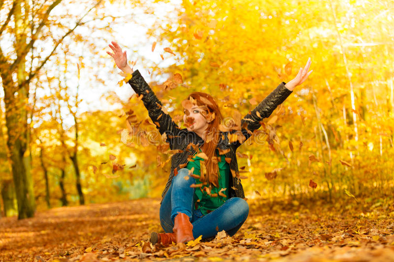 Girl relaxing in autumn park throwing leaves up in the air. Happiness freedom leisure concept. Redhair woman relaxing in autumn park throwing leaves up in the stock photos