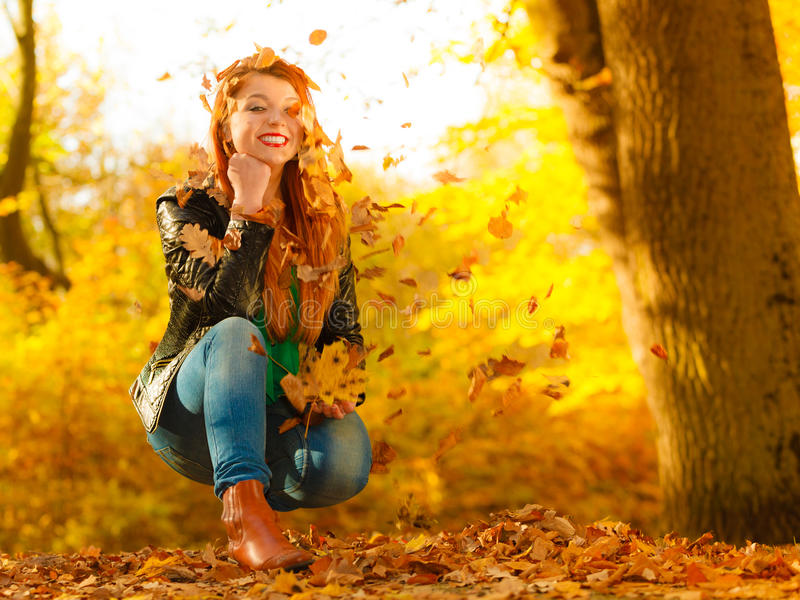 Girl relaxing in autumn park throwing leaves up in the air. Happiness freedom leisure concept. Redhair woman relaxing in autumn park throwing leaves up in the stock image