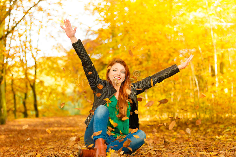 Girl relaxing in autumn park throwing leaves up in the air. Happiness freedom leisure concept. Redhair woman relaxing in autumn park throwing leaves up in the stock photography