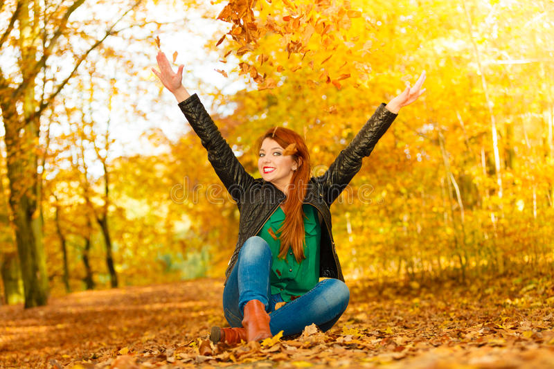 Girl relaxing in autumn park throwing leaves up in the air. Happiness freedom leisure concept. Redhair woman relaxing in autumn park throwing leaves up in the royalty free stock images