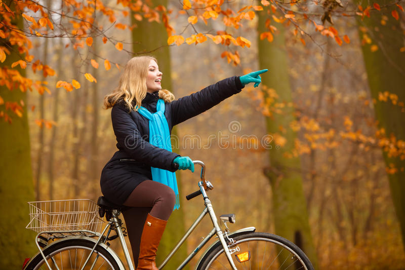 Girl relaxing in autumnal park with bicycle. Fall active lifestyle concept. Beauty young woman girl waering vivid color shawl relaxing in autumnal park with stock photography