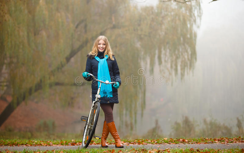 Girl relaxing in autumnal park with bicycle. Fall active lifestyle concept. Smiling young woman girl waering vivid color shawl relaxing in autumnal park with royalty free stock photos