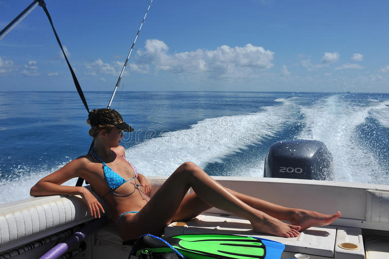 Girl relaxing on the back of motor boat. Cruising on speed at tropical water stock photos