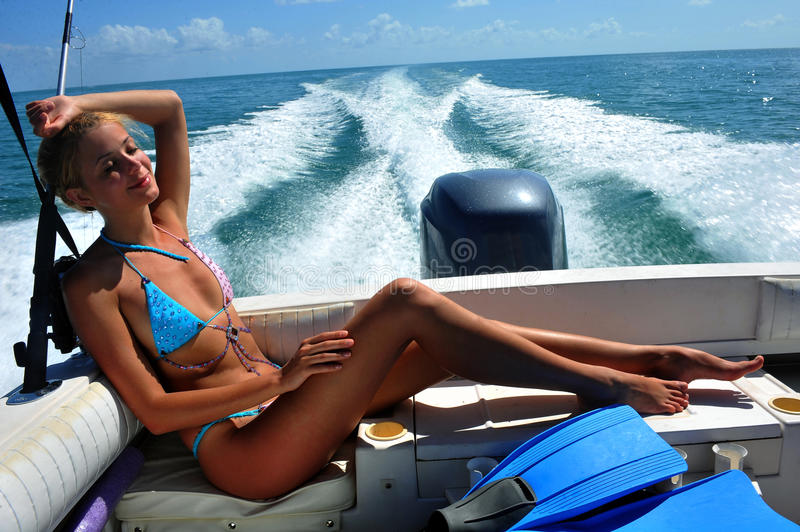Girl relaxing on the back of motor boat. Cruising on speed at tropical water royalty free stock images
