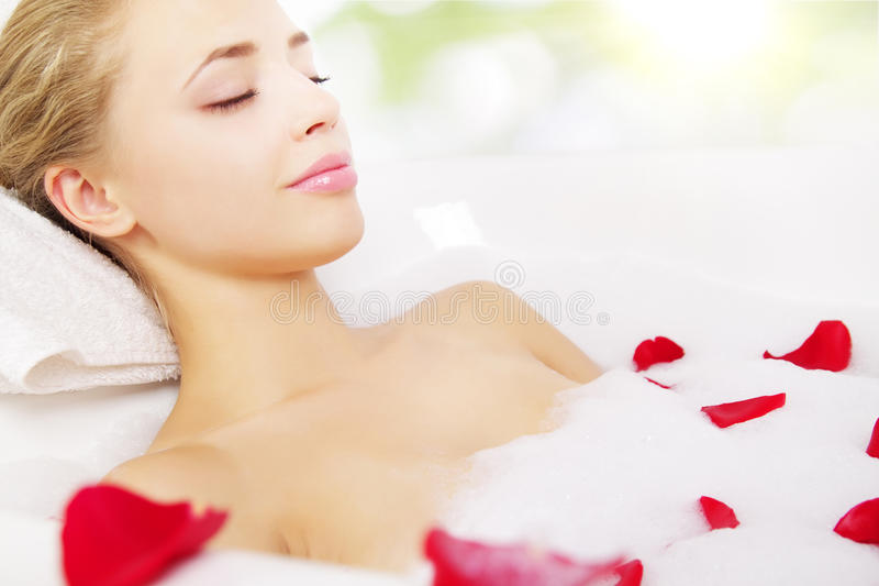 Girl relaxing in bathtub. On light background stock photo