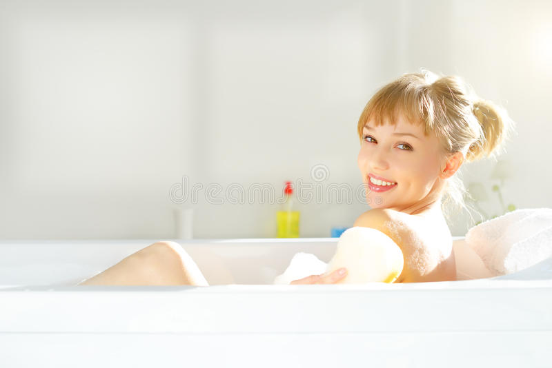 Girl relaxing in bathtub. On light background royalty free stock image