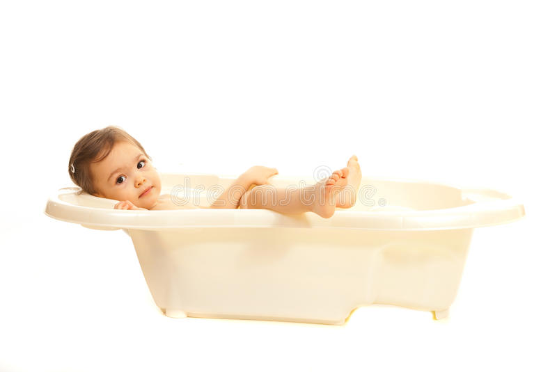 Girl relaxing in a bathtub. Cute toddler girl relaxing in a bathtub isolated on white background royalty free stock photo