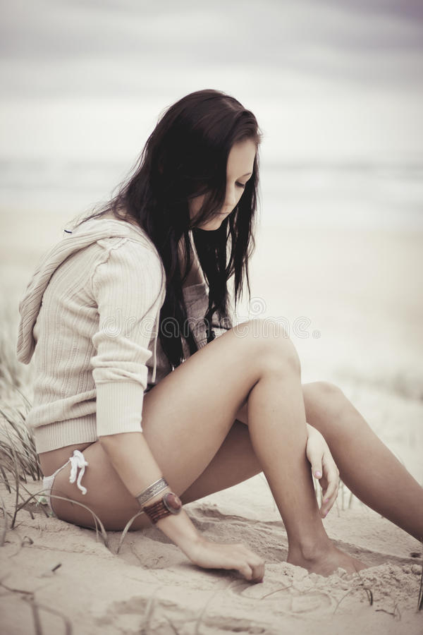 Girl relaxing on beach. Attractive girl relaxing on sandy beach with sea in background stock images