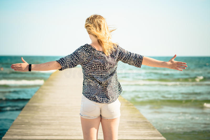 Girl relaxing at beach. Arms wide-open stock image
