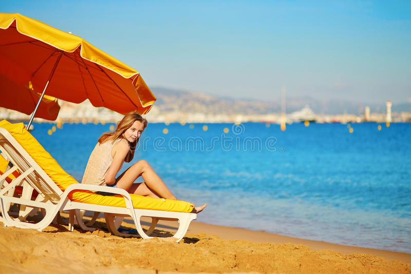 Girl relaxing on a beach chair near the sea. Beautiful girl relaxing on a beach chair near the sea stock photography
