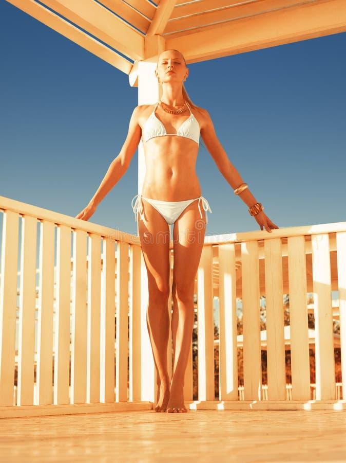 Girl relaxing in a beach gazebo stock image