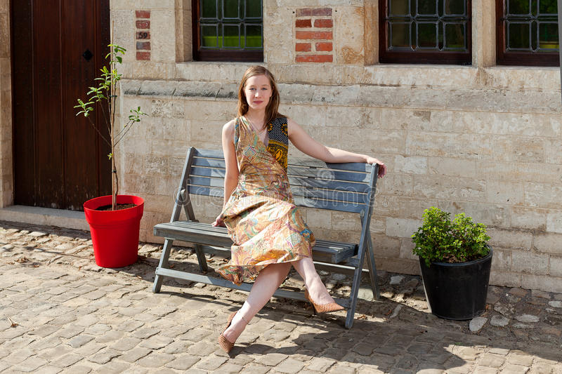 Girl Relaxing On Bench In Front Of Antique House Stock Photo