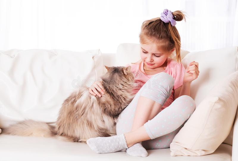 Girl relaxing with cat. Little girl relaxing with adorable cat on the couch royalty free stock photos