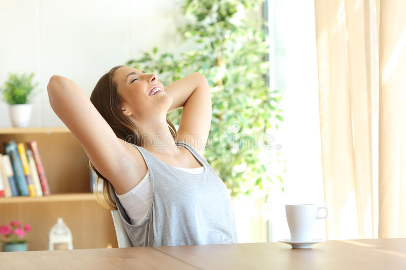 Girl relaxing on a chair at home stock photography