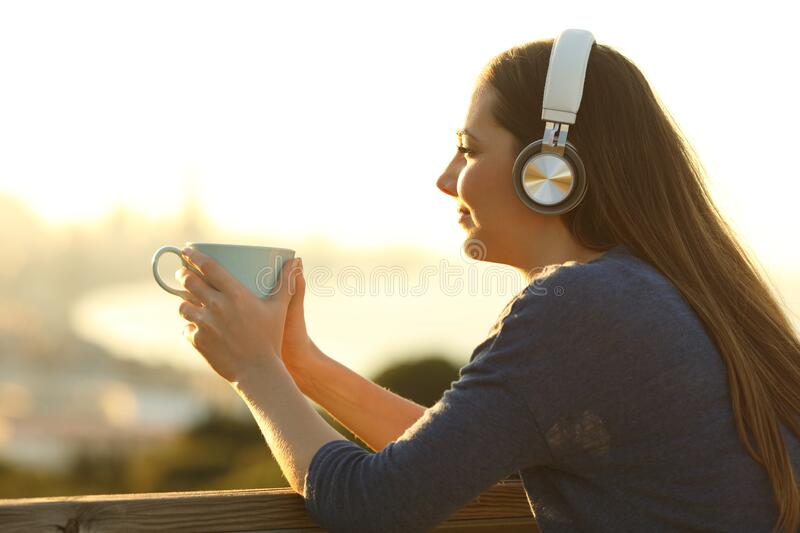 Girl relaxing with a coffee cup listening to music looking away stock image