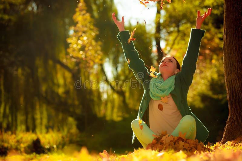 Girl relaxing in colorful forest foliage outdoor. Happiness carefree. woman relaxing in autumn park throwing leaves up in the air with arms raised up. Beautiful royalty free stock photo
