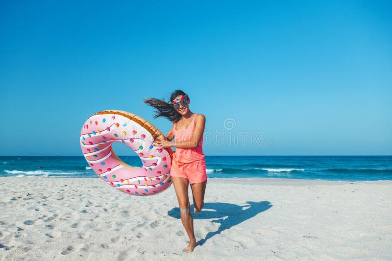 Girl with donut lilo on the beach royalty free stock photo