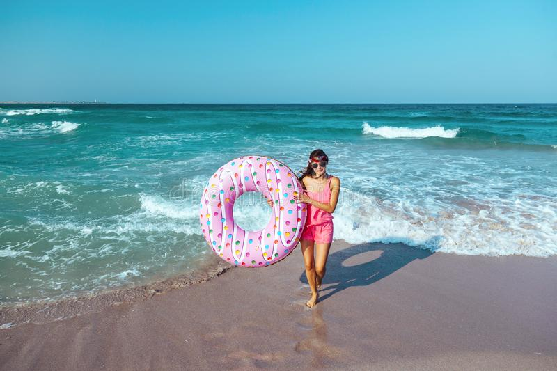 Girl with donut lilo on the beach stock images