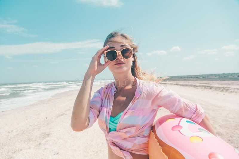Girl relaxing on donut lilo on the beach stock images