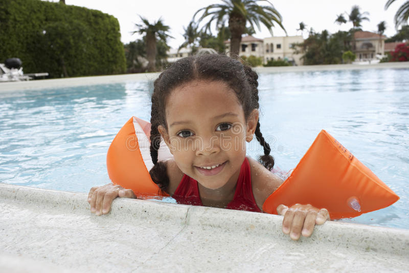 Girl Relaxing On Edge Of Swimming Pool. Portrait of little girl wearing water wings relaxing on edge of swimming pool stock photos
