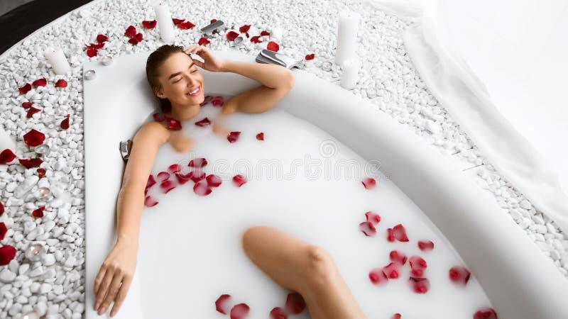 Girl Relaxing In Flower Milk Bath In Resort Spa Salon. Girl Enjoying Flower Milk Bath, Relaxing In Resort Spa Salon stock images