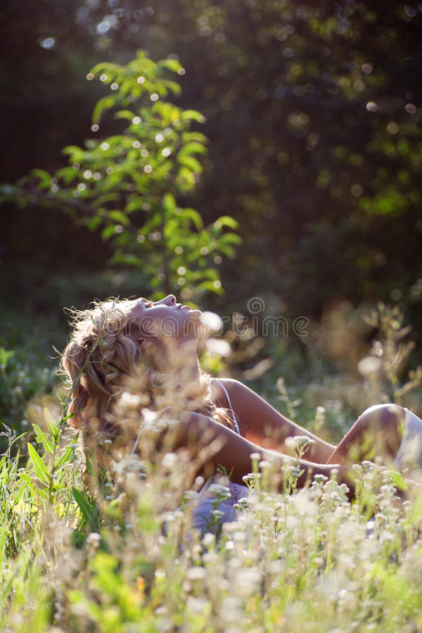 Girl relaxing on green grass in summer day stock photography