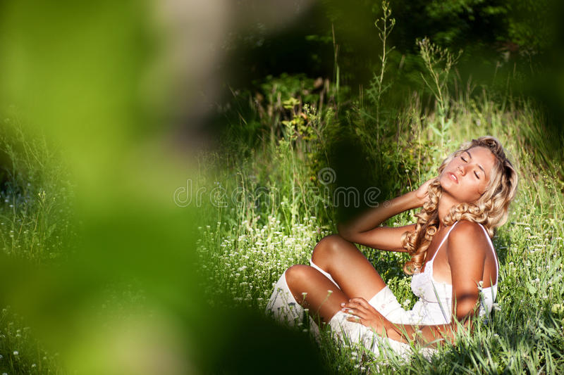 Girl relaxing on green grass in summer day stock photos