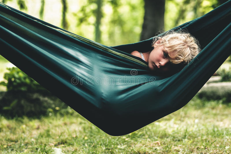 Girl relaxing in a hammock. Blond little girl relaxing in a hammock in the forest stock images