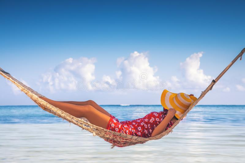 Girl relaxing in a hammock on tropical island beach. Summer vacation in Punta Cana, Dominican Republic stock photos