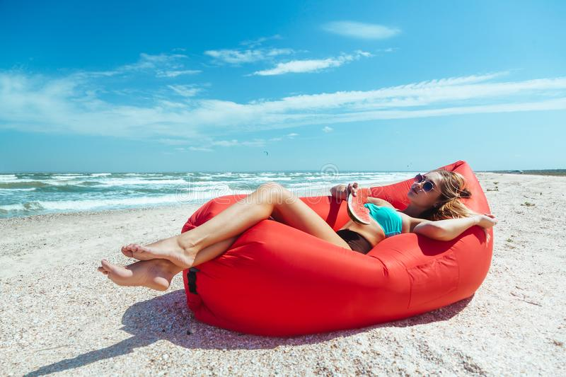 Girl relaxing on lamzac on the beach. Girl relaxing on lamzac and eating watermelon on the beach. Summer holiday idyllic on a tropical island stock photos
