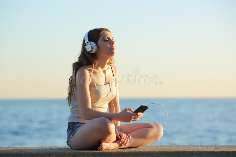 Girl relaxing listening to music from smart phone royalty free stock photos