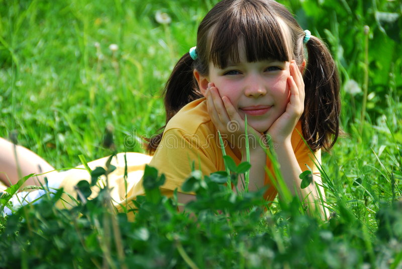 Girl relaxing in meadow. Pretty girl relaxing in meadow with head in hands stock photography