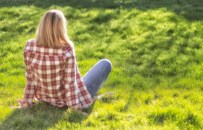 Girl is relaxing on meadow. Blonde beautiful young woman is sitting on the grass and enjoying the sun. Outdoor. Sunny day. Wearing stock photos