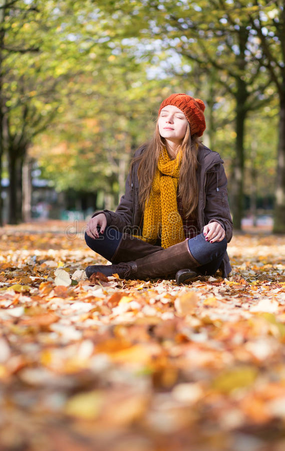 Girl relaxing and meditating in park. On a fall day stock photography