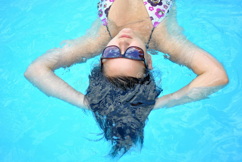 Girl relaxing in pool royalty free stock image