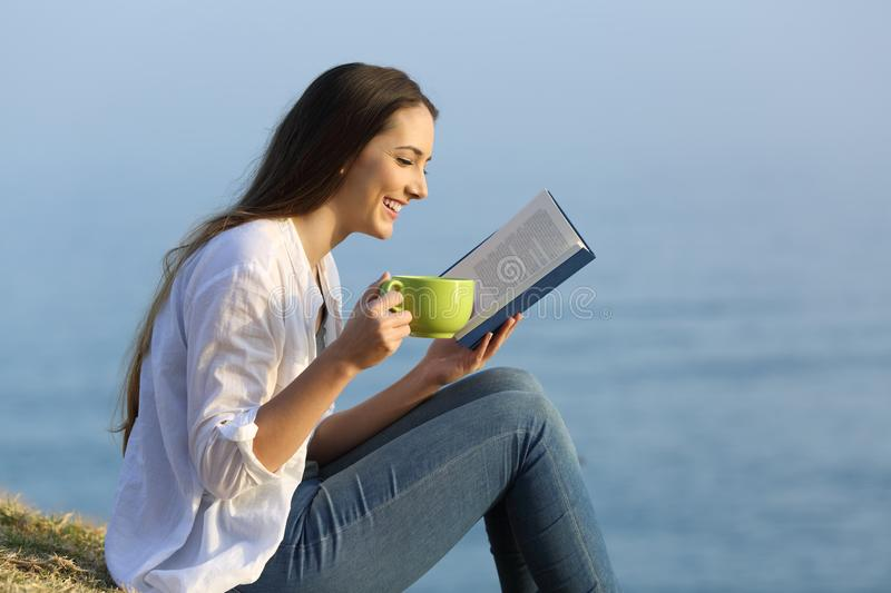 Girl relaxing reading a book and drinking coffee outdoors. Side view portrait of a happy girl relaxing reading a book and drinking coffee sitting on the grass on stock photo