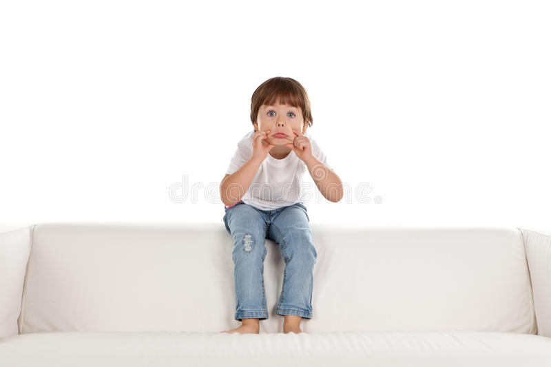 Girl relaxing on settee. Cute young barefoot girl relaxing on comfortable sofa or settee; isolated on white background royalty free stock photo