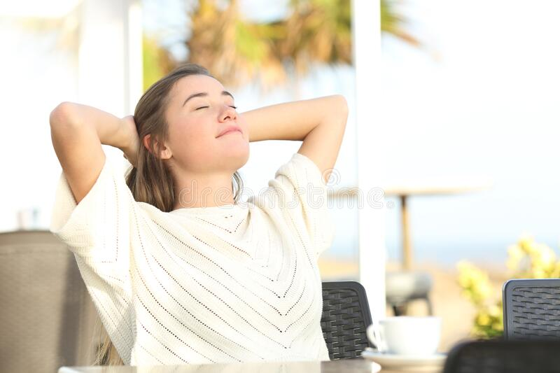 Girl relaxing sitting in a terrace on the beach royalty free stock photo