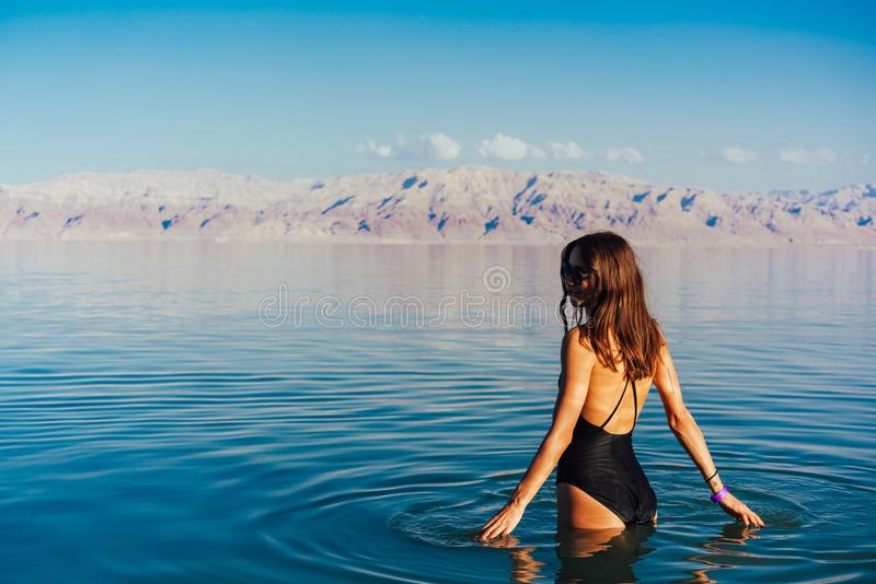 Young woman going to Dead Sea, Israel. Girl is relaxing and swimming in the water of the Dead Sea in Israel stock photo