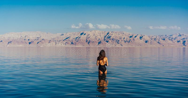 Young woman going to Dead Sea, Israel. Girl is relaxing and swimming in the water of the Dead Sea in Israel stock photography
