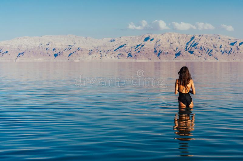 Young woman going to Dead Sea, Israel. Girl is relaxing and swimming in the water of the Dead Sea in Israel stock images